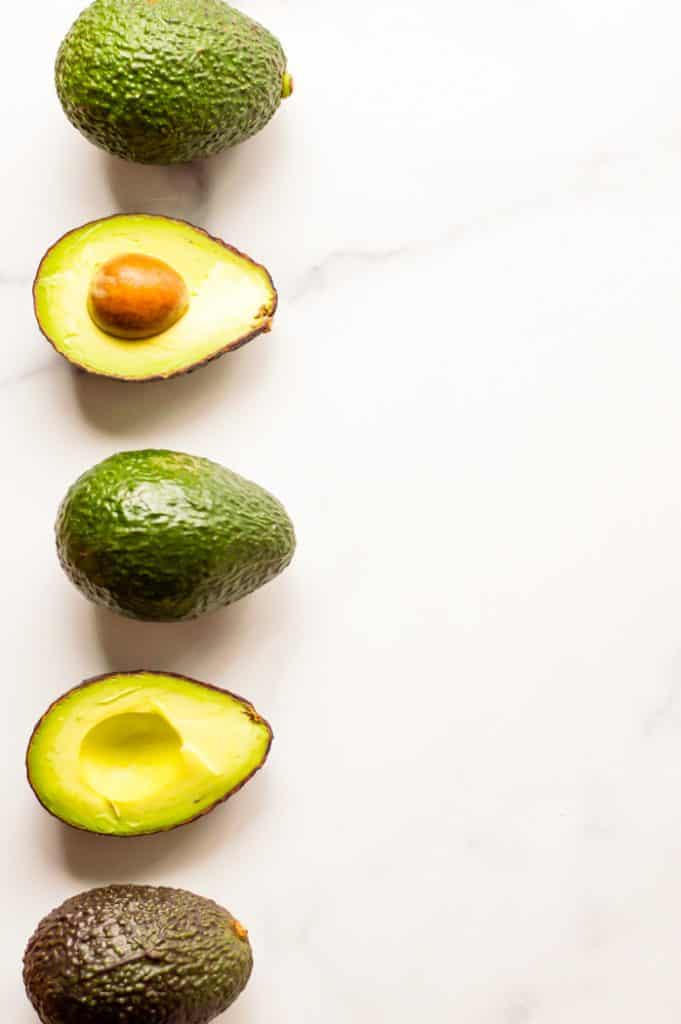 Avocados, lined up on the left side of the image. Some of the avocados are sliced to revel the flesh and pit inside and other avocados are whole.