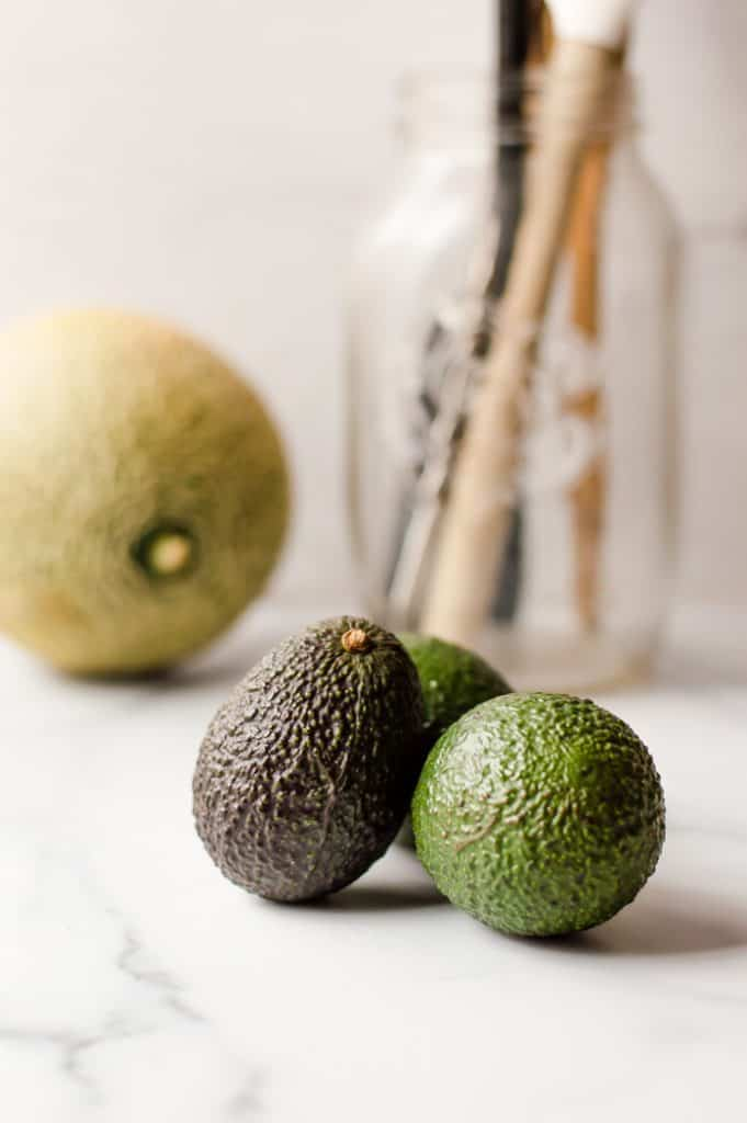 3 unripe avocados on a white marble top with a cantaloup and glass jar or cooking utensils in the background.