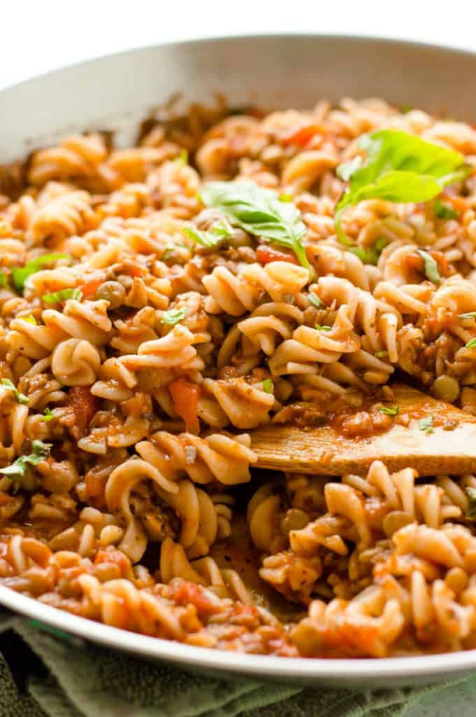 Serving Mushroom Lentil Pasta in a big grey bowl and decorating it with healthy herbs
