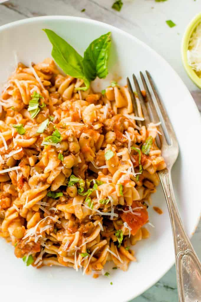 A big metal fork inside the plate full of the prepared Mushroom Lentil Pasta with fresh herbs mixed with the delicious sauce