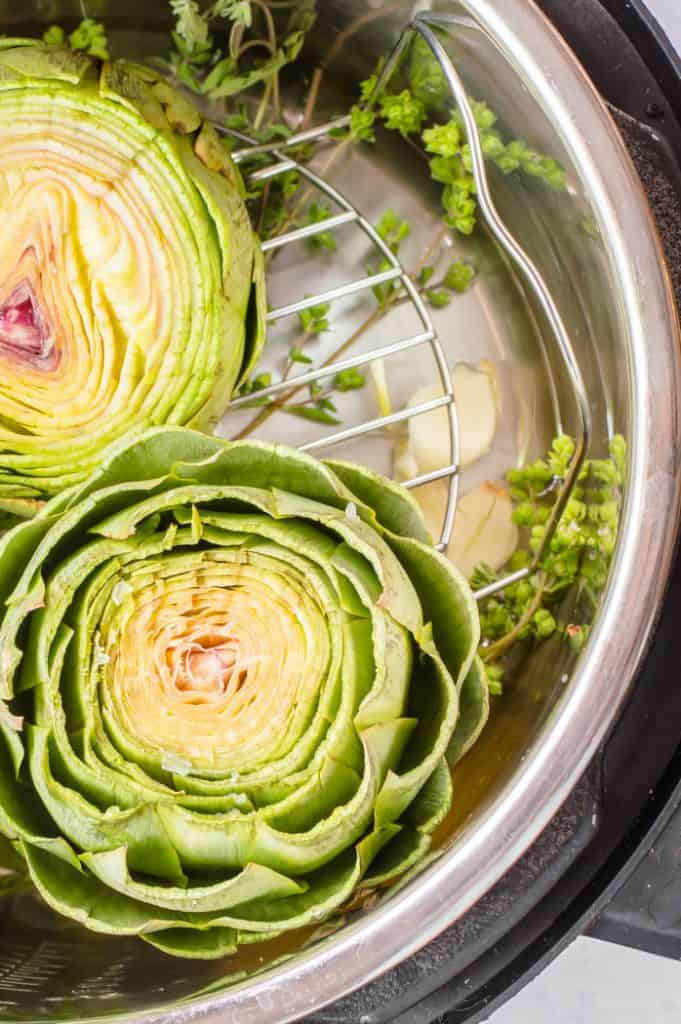 Two prepped artichokes in an Instant pot before being cooked.
