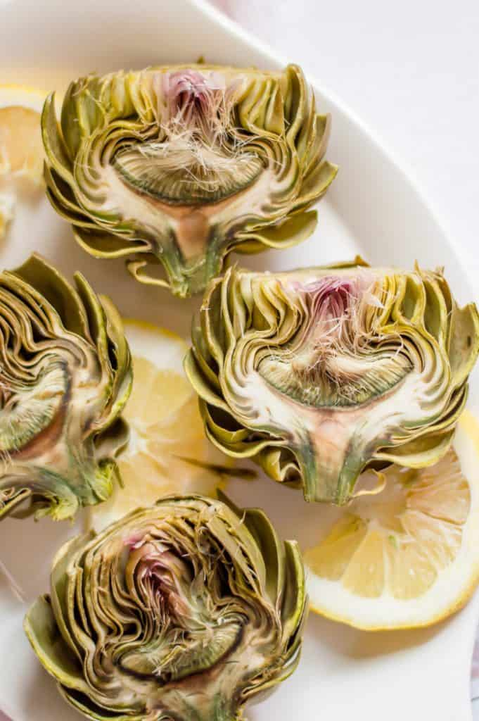 Cooked artichokes sliced in half and arranged on a white plate with slices of lemon.