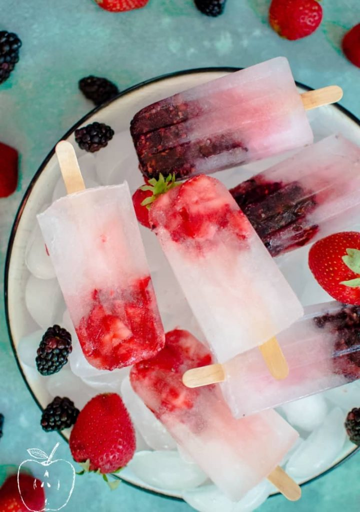 Berry hydrating popsicles in a bowl of ice with berries scattered around.