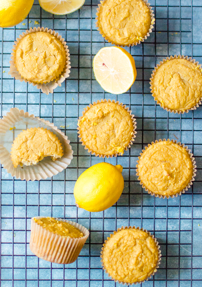 Lemon Paleo Muffins on a cooling rack with sliced lemons.