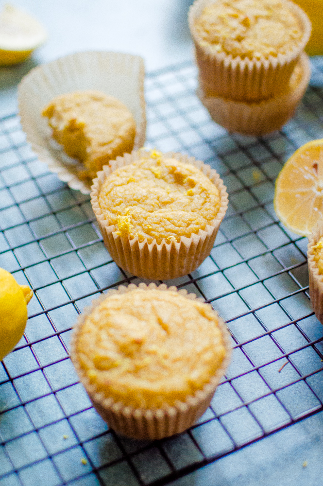 Lemon Paleo muffins cooling on a rack. One muffin has a bite taken out of it.