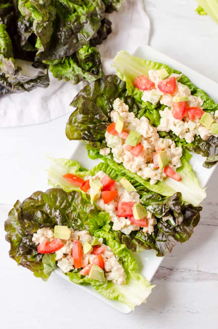 Healthy mashed chickpea salad served in four lettuce boats with more lettuce in another plate