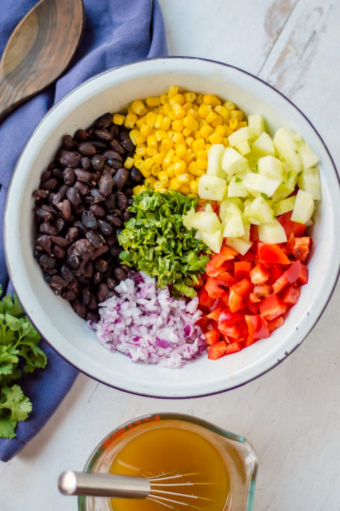 The ingredients from corn and black bean salad in a bowl before mixing. A blue napkin and wooden spoon are on the side and the dressing is in a measuring cup next to the bowl.