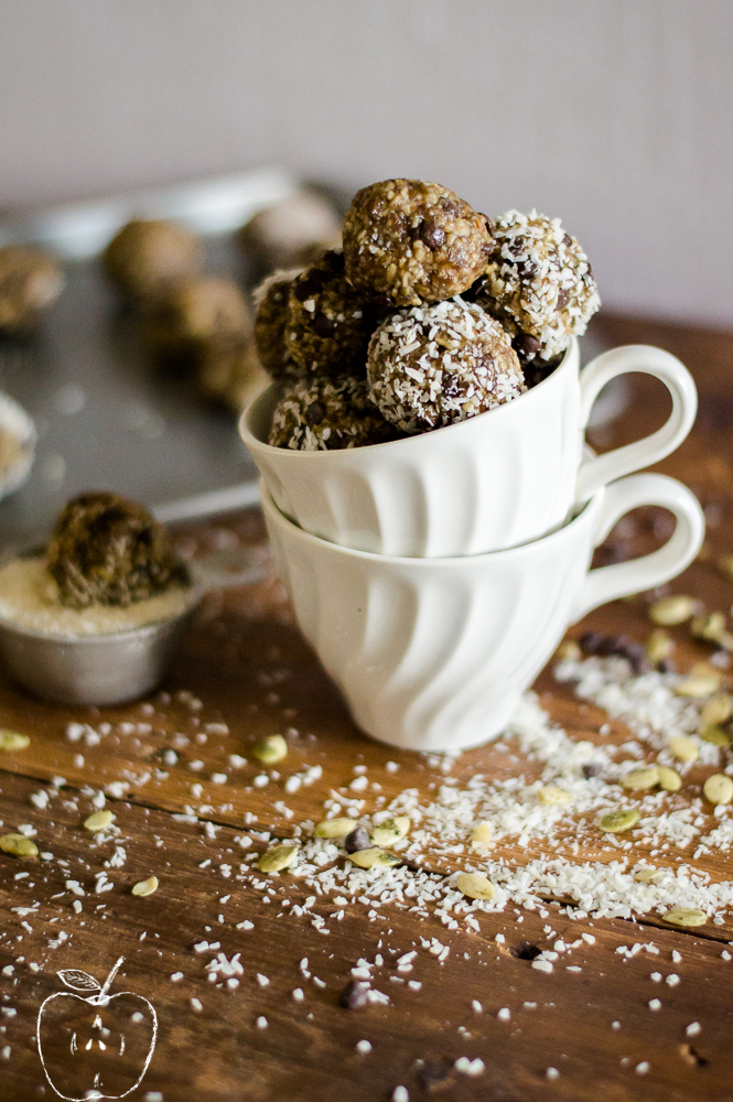 No-Bake Chocolate Chip Cookie Bites stacked in a white tea cup with some more in the background.