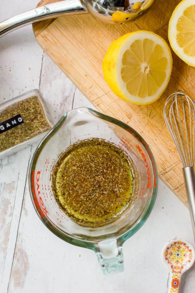 The dressing for Greek Quinoa Salad in a measuring cup with a whisk, sliced lemon and herbs next to it.