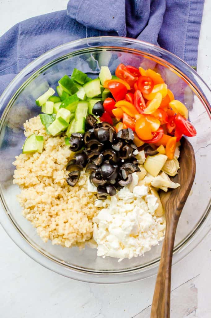 The ingredients for Greek Quinoa Salad in a bowl before mixing with a wooden spoon resting on the side of the bowl.