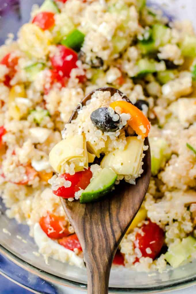 Greek quinoa salad on a wooden spoon with the rest of the salad in a bowl in the background.