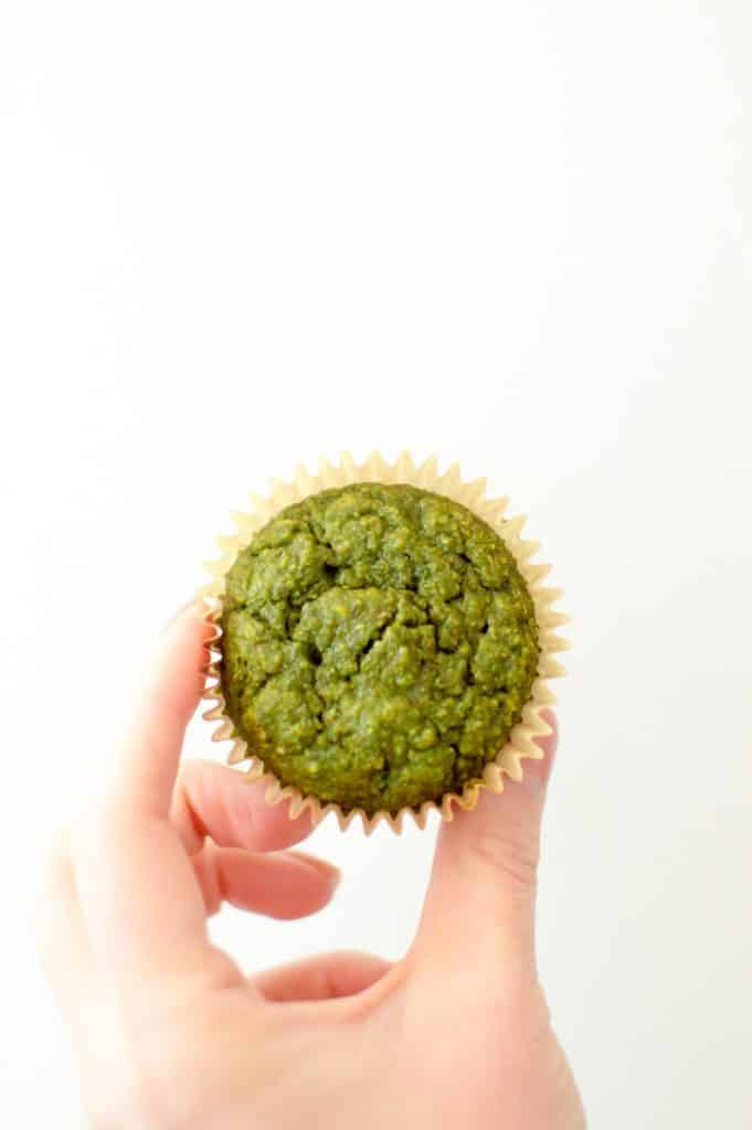 A hand holding a single green smoothie muffin up after it is done cooking.
