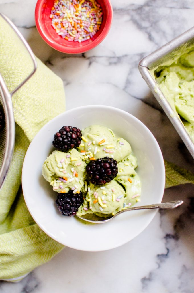 A bowl of green smoothie nice cream topped with black berries and sprinkles.