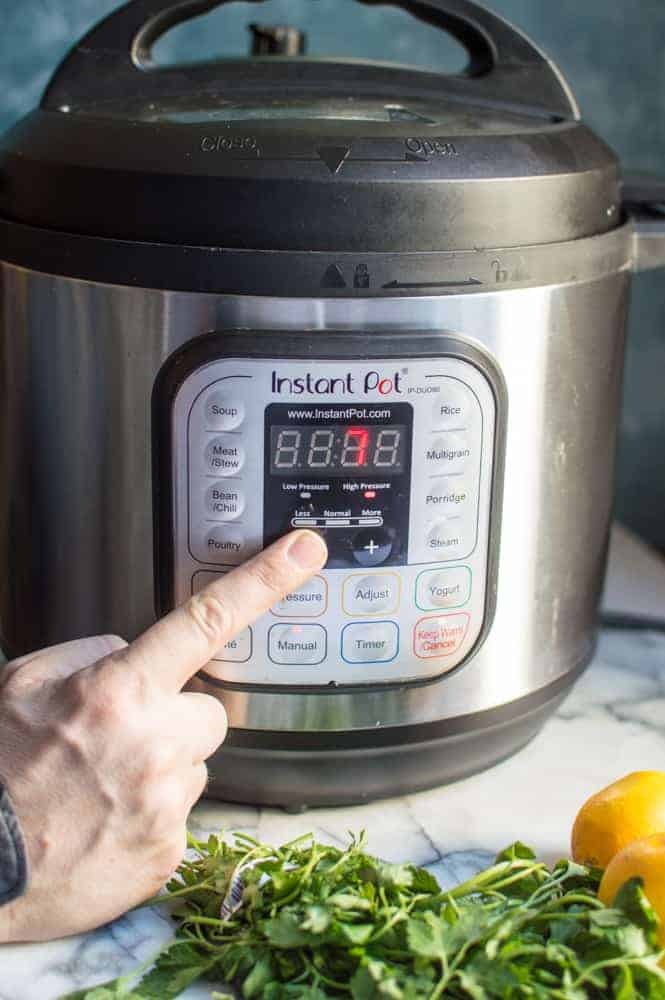 A finger pressing the buttons on a closed instant pot.
