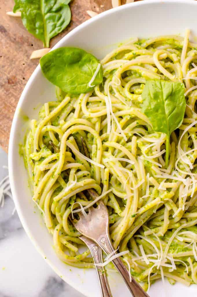 A bowl of pasta coated with spinach pesto. Two forks are in the bowl and it is topped with extra shredded cheese and a few loose leaves of spinach.