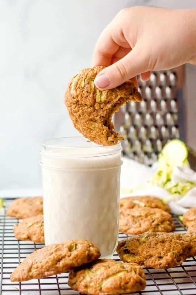 A zucchini almond butter cookie with a bite taken out of it being dunked in a glass of milk. The glass is on a cooling rack with other cookies surrounding it.