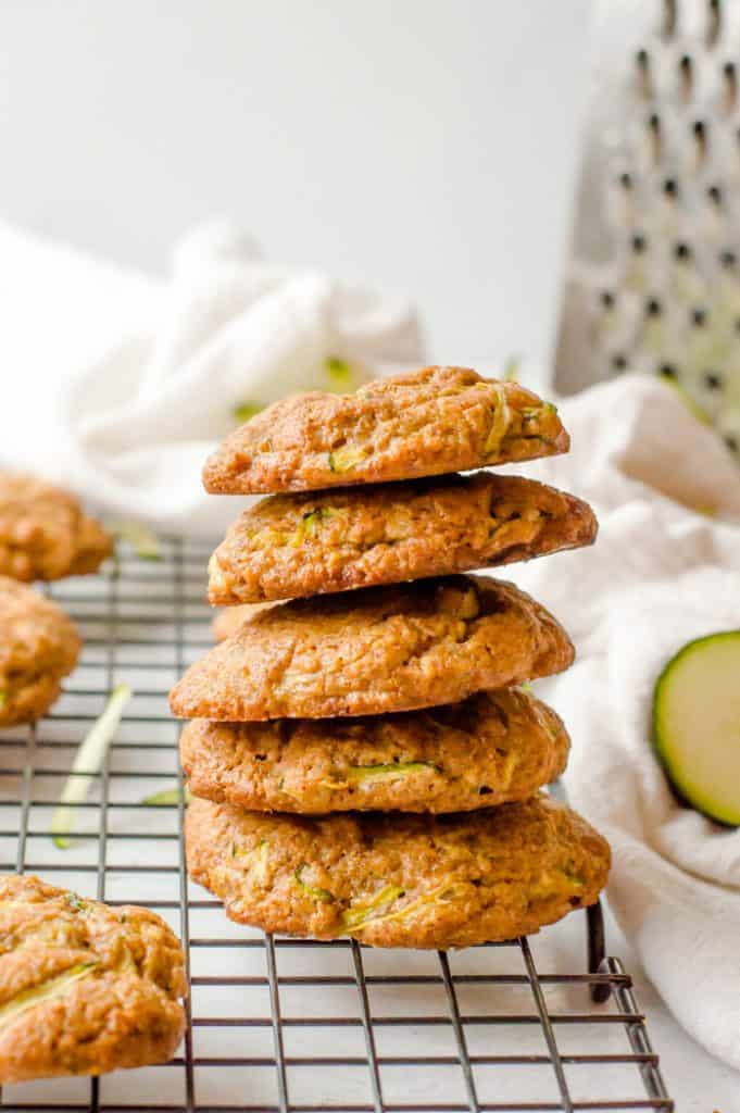 Zucchini almond butter cookies stacked on a cooling rack with a grater in the background and other cookies around it.