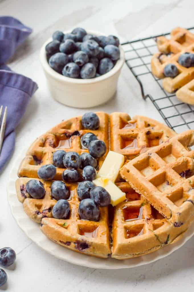 A blueberry zucchini waffle on a plate topped with butter, syrup and fresh blueberries. There is a bowl of blueberries next to the plate and a fork and blue napkin on the side.
