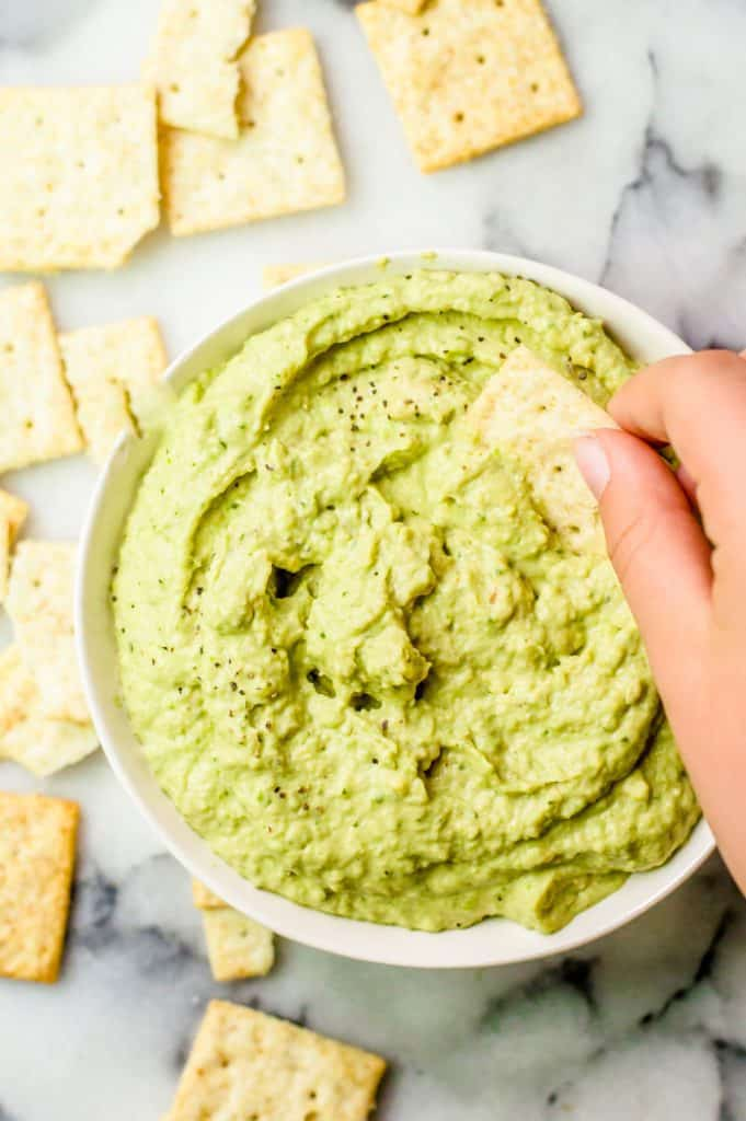 A bowl of zucchini avocado dip with a hand dipping a cracker in it and other crackers scattered around.