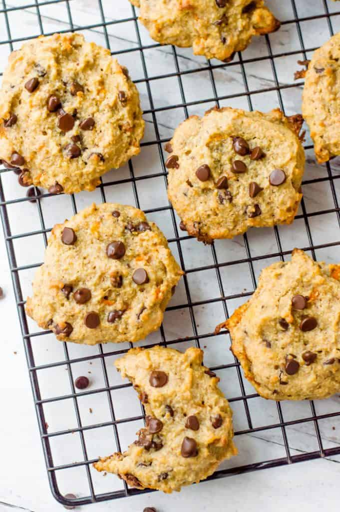 Carrot Paleo Chocolate chip cookies on a cooling rack. One cookie has a bite taken out of them.