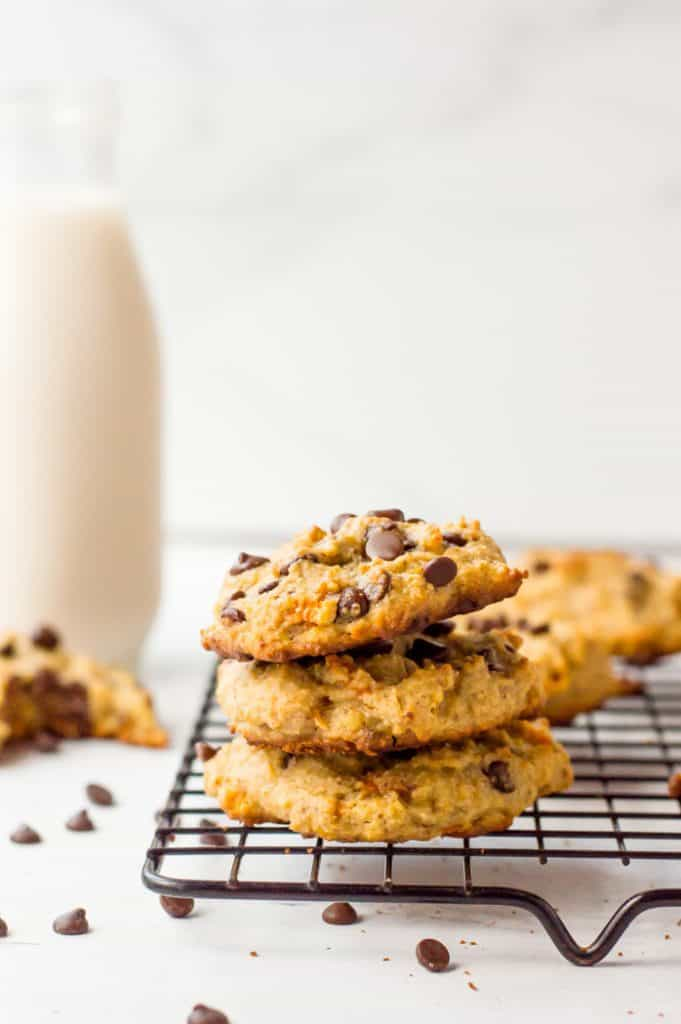 A stack of three Paleo chocolate chip cookies on a cooking rack with a glass jug of milk in the background.