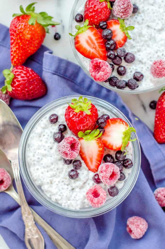 Two bowls of coconut chia pudding with berries on top and scattered around the bowls. There is a spoon next to one bowl