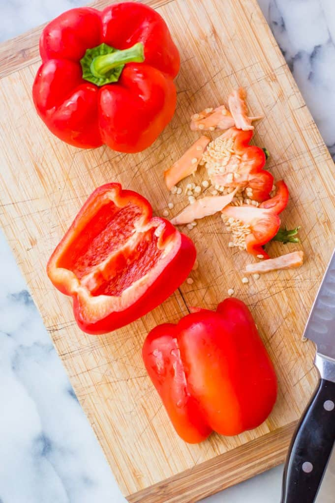 Two red bell peppers on a cutting board with one cut in half with stem, seeds and membrane removed.