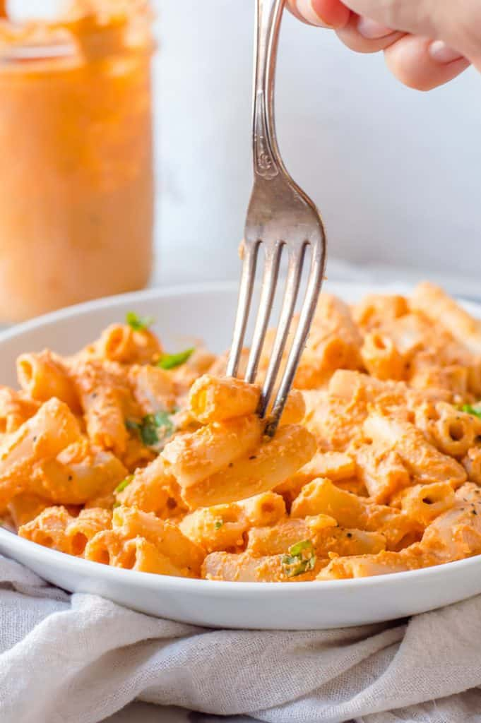 A fork taking a bite of pasta covered in roasted red pepper sauce from a bowl. There is a jar of red pepper sauce in the background.