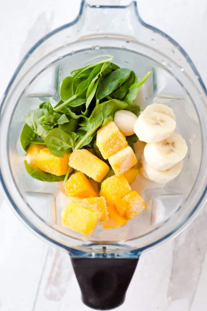 Ingredients for simple spinach mango smoothie in the blender before blending.