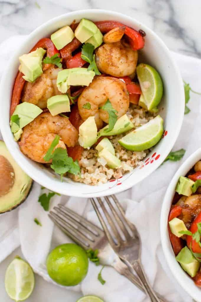 A veggie-loaded shrimp taco bowl on a white table cloth with fresh cilantro over the top and forks next to the bowl.