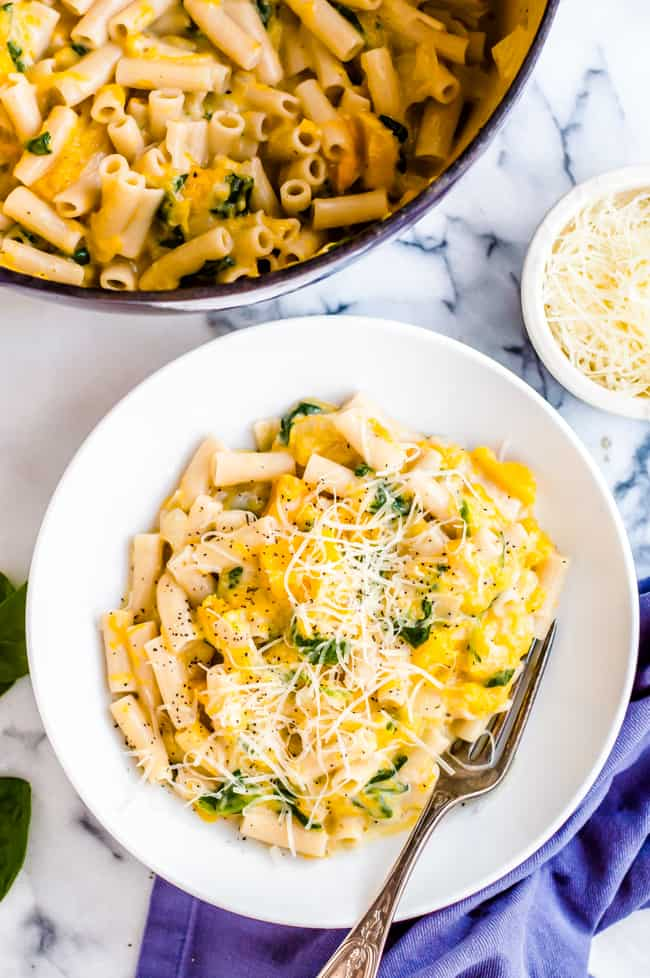 A bowl of cheesy butternut squash pasta with a fork and topped with parmesan cheese and black pepper. The pot of pasta and a bowl of cheese are on the side.