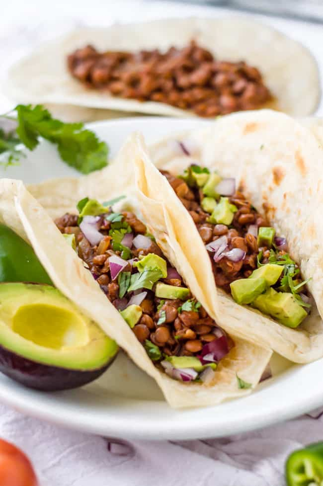 Vegan slow cooker lentil tacos on a plate in tortillas. They have onion, avocado and cilantro sprinkled on top. A jalapeño and avocado are on the plate too.
