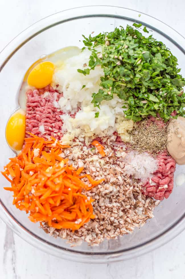 The ingredients for veggie-loaded mini meatloaves in a bowl before mixing.