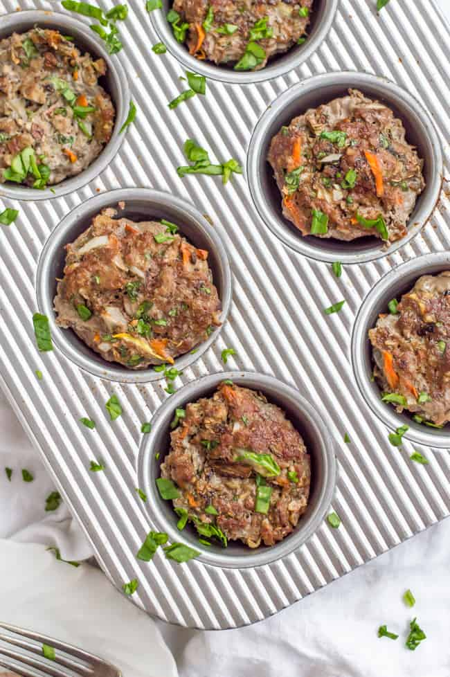 A muffin tin of veggie-loaded mini meatloaves after cooking and topped with finely chopped spinach.