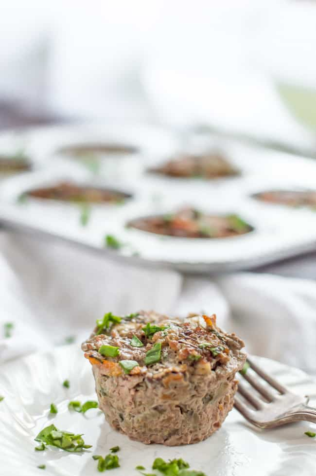 A single veggie-loaded mini meatloaf on a plate topped with chopped spinach and with a fork. A muffin tin with other meatloaves is in the background