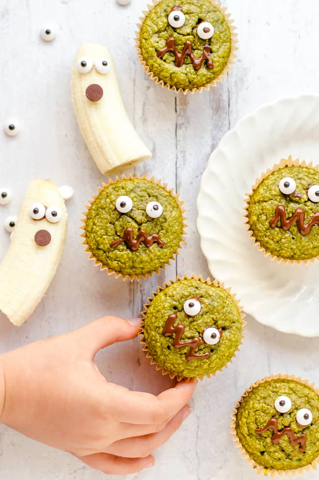 Oatmeal Green Smoothie muffins decorated like monsters with sugar eyes and melted chocolate mouths.  Bananas decorated like ghosts are next to them and a child's hand is taking one.