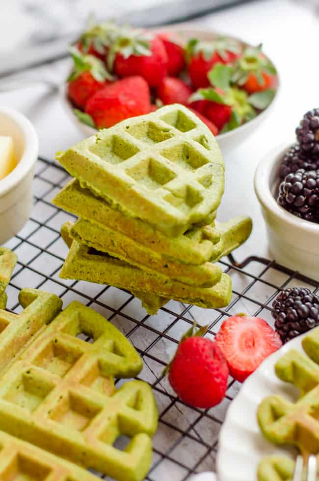 Green smoothie waffles stacked on top of one another on a cooling rack.