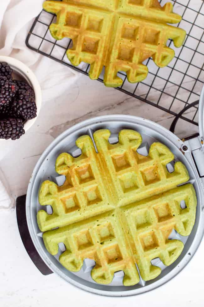 A green smoothie waffle cooking on the waffle iron. One waffle is on the cooling rack next to it and a bowl of blackberries is on the side.