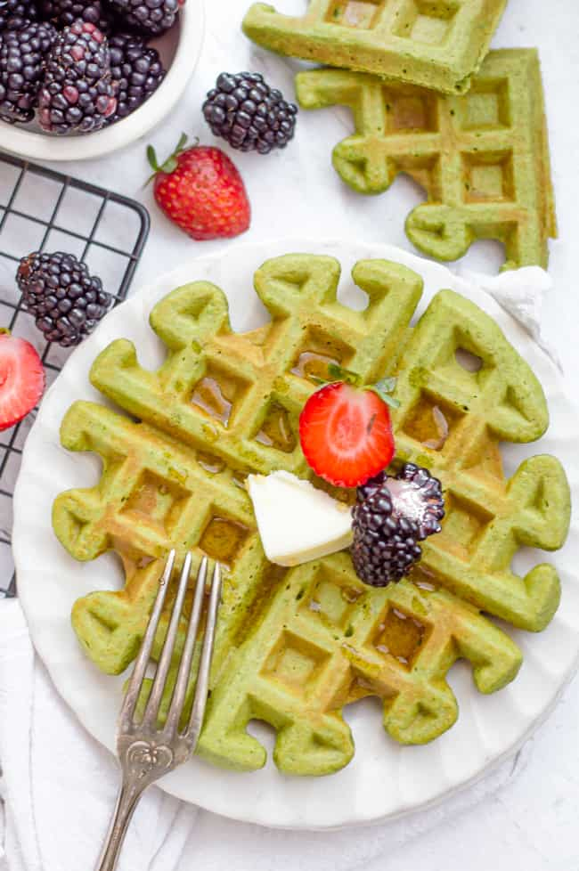 Green smoothie waffles on a plate with butter, strawberry and black berry on top.