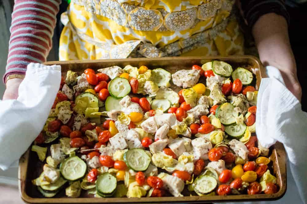Sheet pan Greek Chicken and Veggies being held by a person, fresh from the oven.