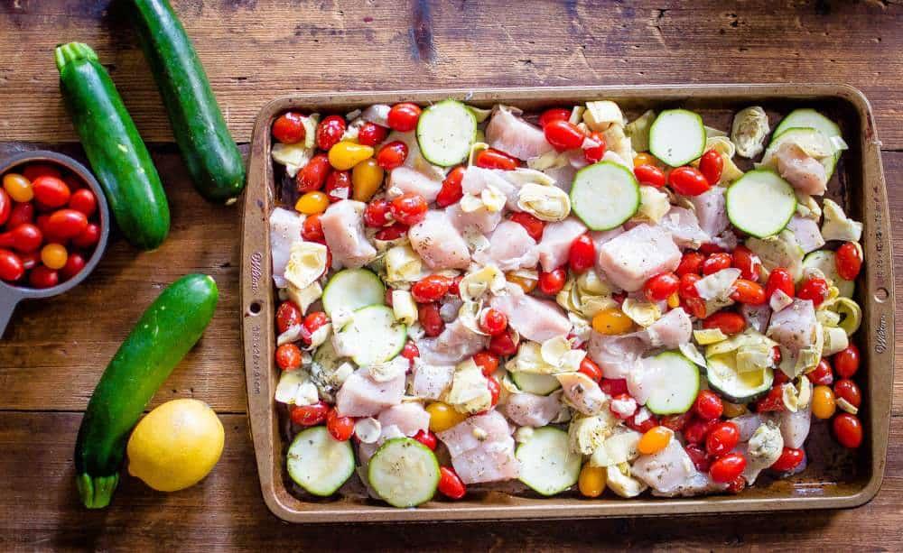 sheet pan greek chicken and veggies on sheet pan before cooking.