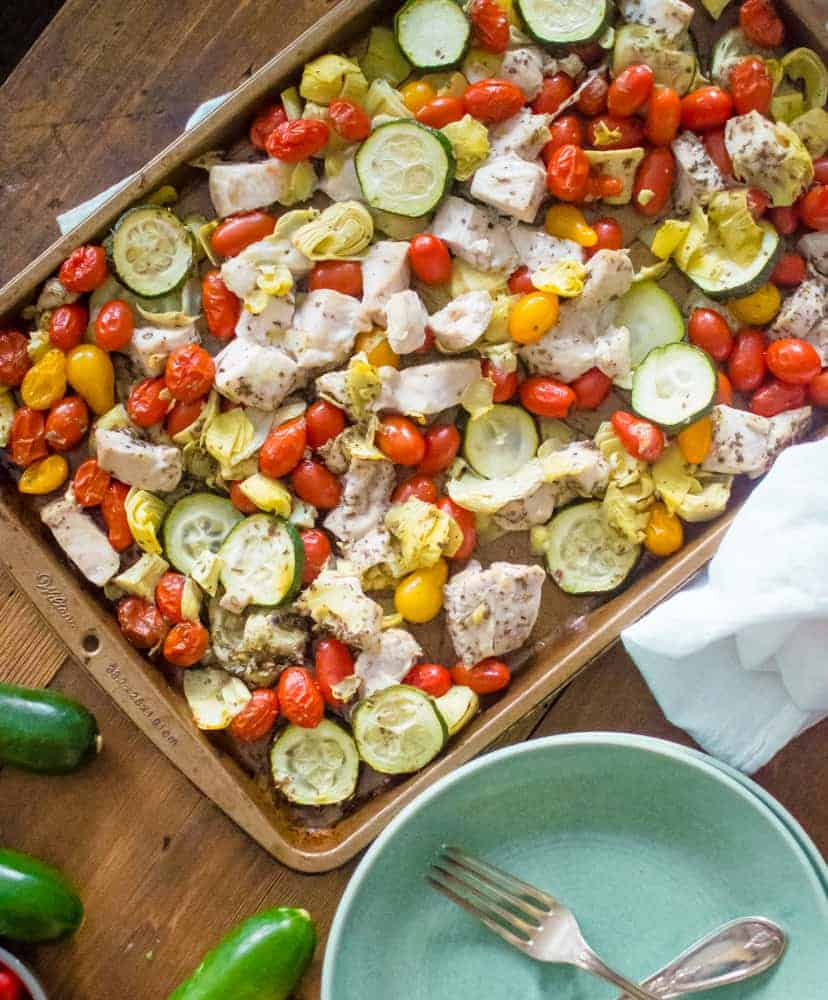 Sheet pan Greek chicken and veggies   on the table with plates, ready to be served up.