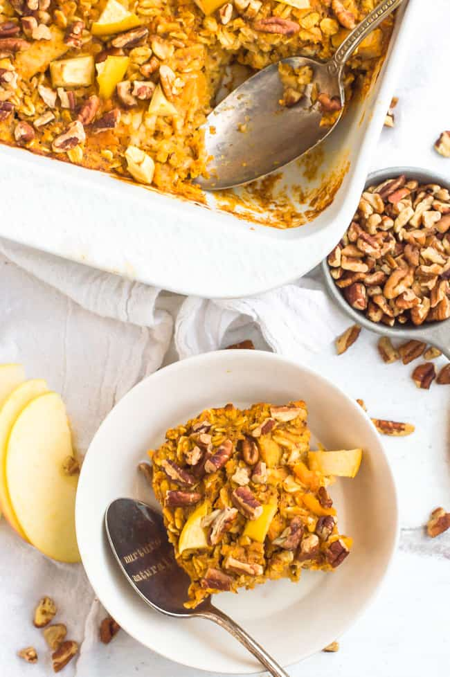 Apple sweet potato baked oatmeal in a dish with a spoon. a bowl of nuts and the tray of the baked oatmeal are in the background.