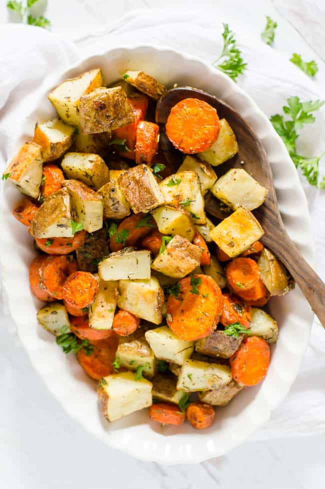 A bowl of roasted carrots and potatoes with fresh parsley sprinkled on top with a wooden spoon on the side.