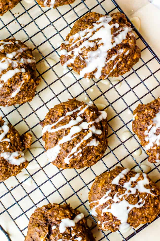 Soft carrot gingerbread cookies on a cooling rack. They are drizzled with maple icing.