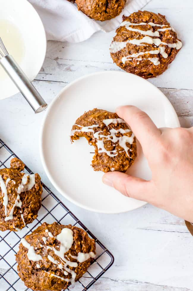 A soft carrot gingerbread cookie on a plate with a bite taken out of it. A hand is taking the cookie and there are other cookies on a cooling rack next to it and on the table.