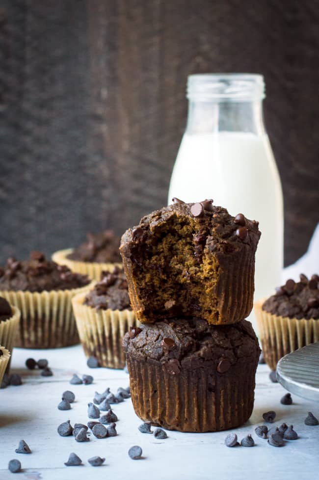 Two chocolate protein muffins stacked on top of one another. The top one has a bite out of it and there are other muffins and a glass of milk in the background.