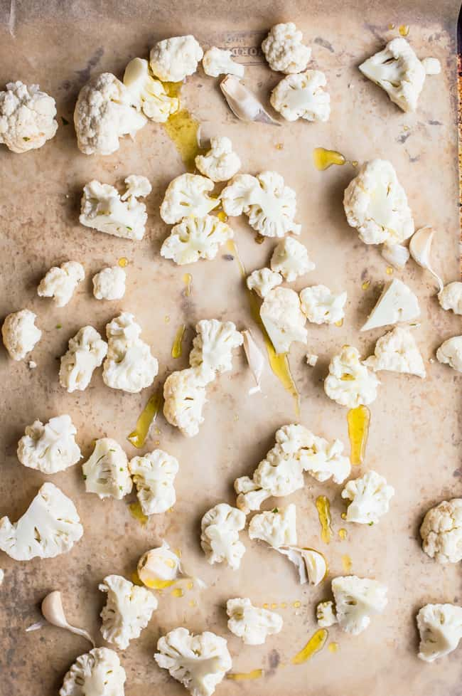 Cauliflower florets on a baking sheet drizzled with olive oil.