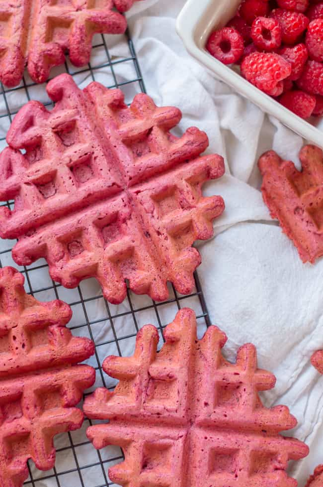 vegan beet waffles on a cooling rack. There is a container of raspberries next to them and a white napkin under the cooling rack.