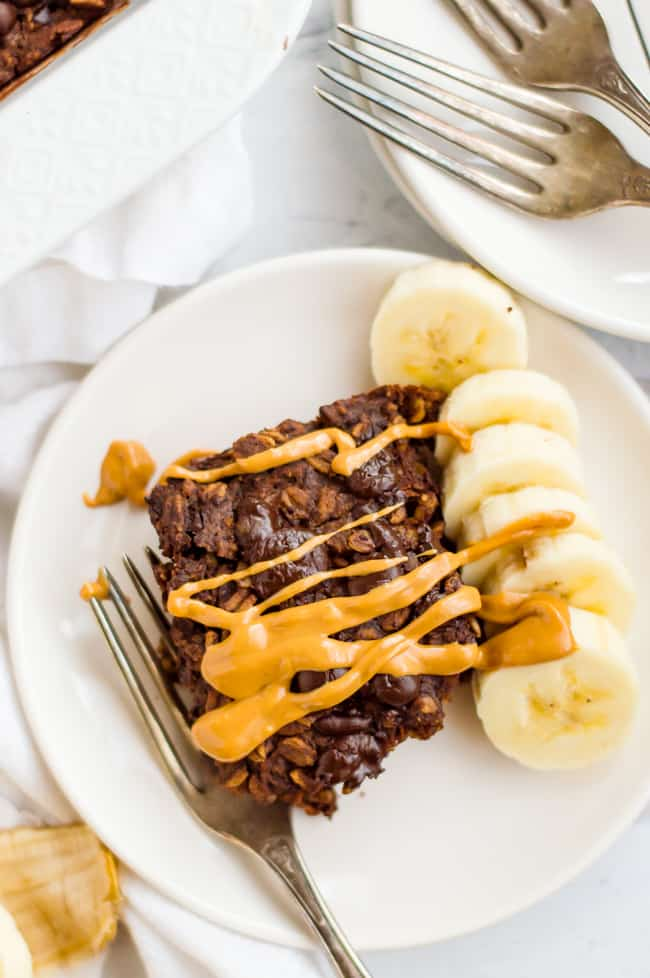 A slice of chocolate baked oatmeal on a plate with peanut butter drizzled over the top, sliced banana next to it and a fork on the plate. The tray of the baked oatmeal is next to the plate and so are extra forks and plates.